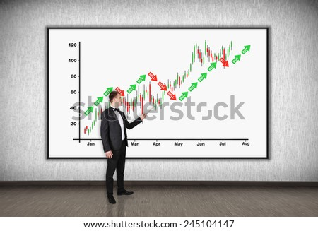 businessman with a pointer points to a stock chart - stock photo
