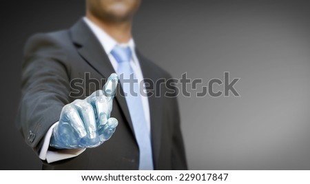 Businessman with a robot hand using a digital interface - stock photo