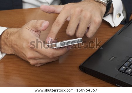 Businessman with a smart phone and laptop - stock photo