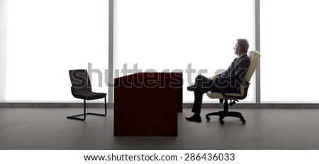 Businessman with an empty chair waiting for a late client.  He looks upset and stressed.  The lonely mood is set by the back light from the large windows. - stock photo