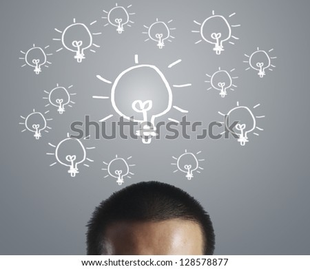 Businessman with an idea, drawn light bulb - stock photo