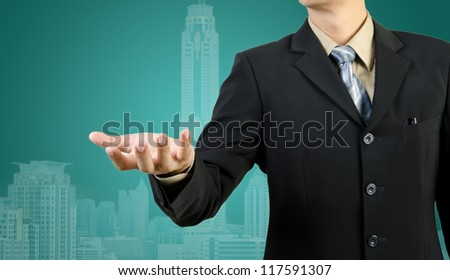 businessman with an open hand ready on city background - stock photo