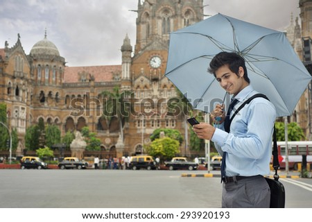 Businessman with an umbrella reading an sms - stock photo