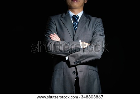 Businessman with arms crossed in front - stock photo