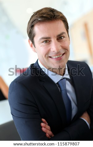 Businessman with arms crossed looking at camera - stock photo