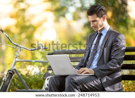 Businessman with bicycle working on laptop on bench in park - stock photo