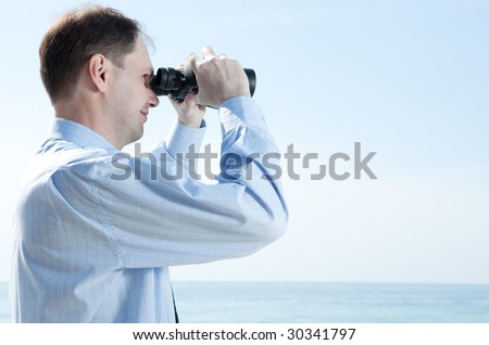 Businessman with binoculars against blue sky - stock photo