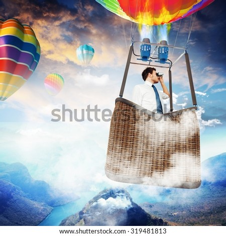 Businessman with binoculars in hot air balloon - stock photo
