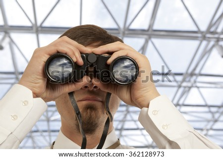 Businessman with binoculars. Over blue background. - stock photo