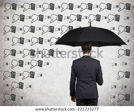 Businessman with black umbrella standing under the drawn storm of negative information. Photo over concrete background. A concept of  risk avoidance.  - stock photo