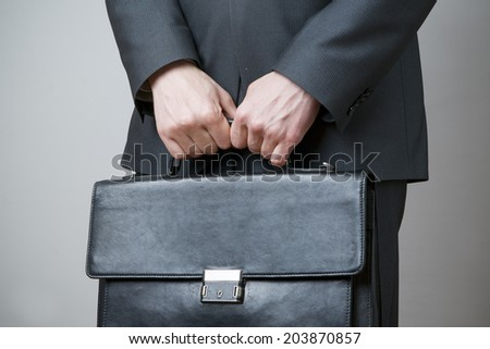 Businessman with briefcase in hand on gray background - stock photo