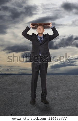 Businessman with briefcase under a stormy sky - stock photo