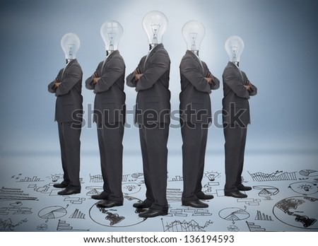 Businessman with bulb head multiplied standing on floor of graphs on blue background - stock photo