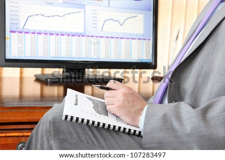 Businessman with Business plan.  Male hand with pen  on the  Business plan in front of computer screen with financial data and charts - stock photo