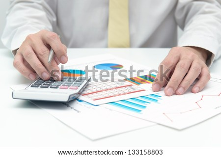 Businessman with calculator doing business data analysis - stock photo