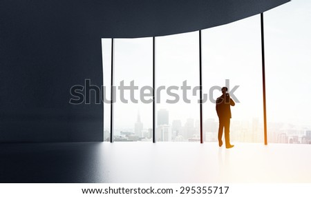 businessman with cell phone in big sunlight office - stock photo