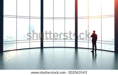 businessman with cellphone in big sunlight office - stock photo