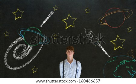 Businessman with chalk universe planet solar system on blackboard imagining space travel - stock photo