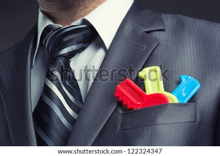 Businessman with colorful toy keys in suit pocket - stock photo