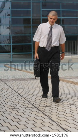 Businessman with computer bag walking in front of a corporate building - stock photo