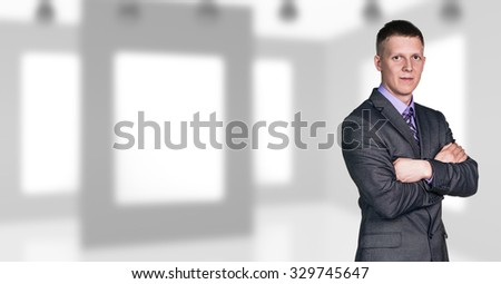 Businessman with crossed arms stands on the office background - stock photo