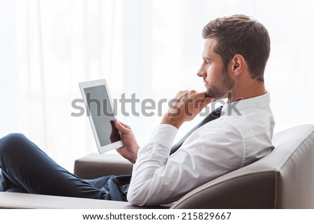 Businessman with digital tablet. Side view of confident young businessman in shirt and tie working on digital tablet while sitting at the chair - stock photo