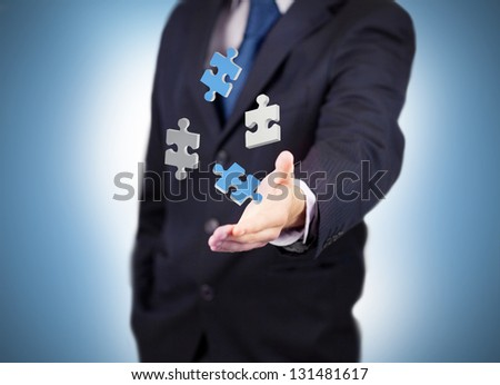Businessman with digital white and blue puzzles levitating - stock photo