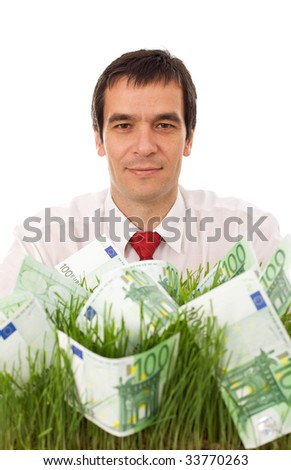 Businessman with euro banknotes in grass - green business concept, isolated - stock photo