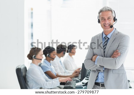 Businessman with executives using computers in office - stock photo