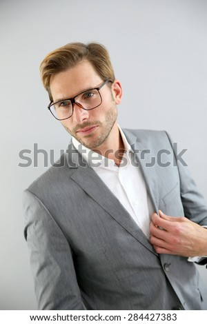 Businessman with eyeglasses standing on grey background, isolated - stock photo