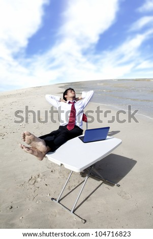 Businessman with feet over the table relaxing at the beach - stock photo