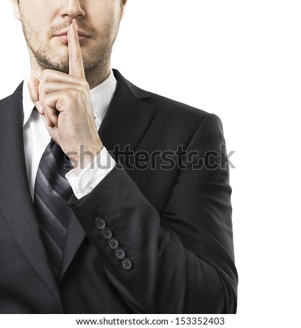 Businessman with finger on lips asking for silence - stock photo