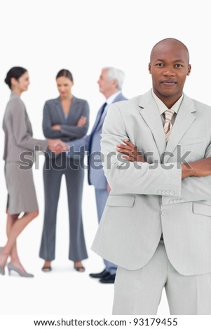 Businessman with folded arms and trading partners behind him against a white background - stock photo