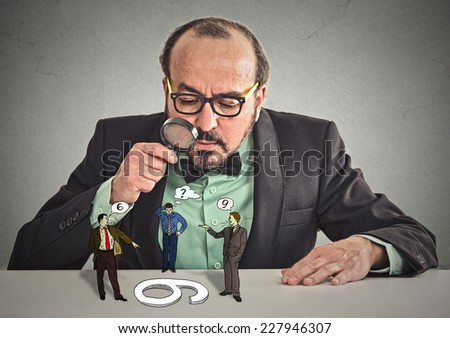 Businessman with glasses sitting at desk skeptically looking at arguing people through magnifying glass isolated grey office wall background. Human face expression, attitude. To each its own concept - stock photo