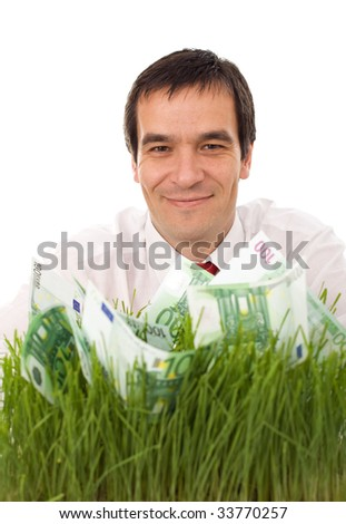 Businessman with green banknotes in the grass - isolated environment friendly business concept - stock photo
