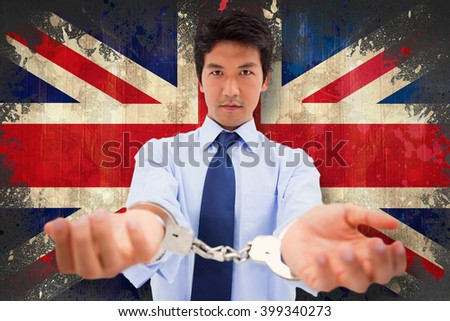 Businessman with handcuffs against union jack flag in grunge effect - stock photo