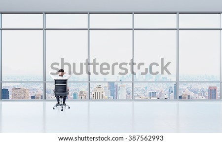 Businessman with hands on back of head sitting in front of panoramic window, Paris view. Office. Concept of rest at work. - stock photo