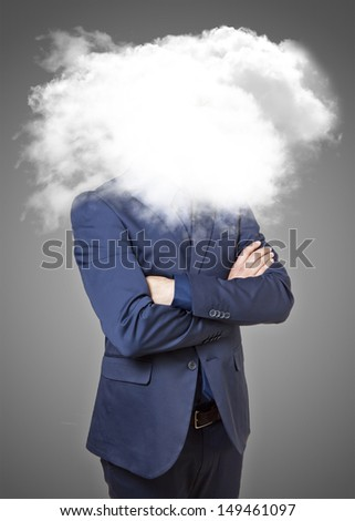Businessman with head in the clouds on a grey background - stock photo