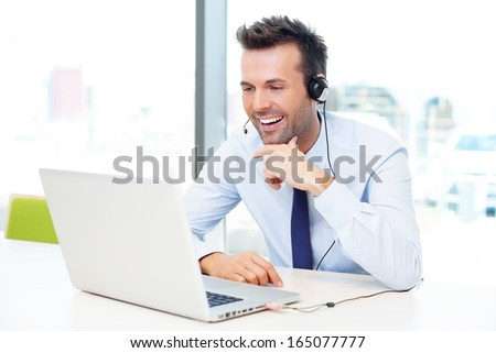 Businessman with headset talking using his laptop - stock photo