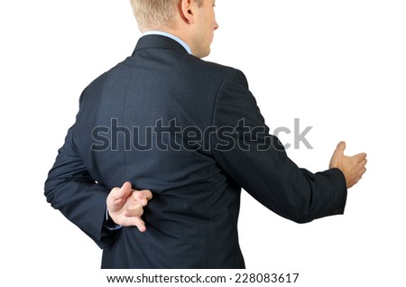 Businessman with his fingers crossed behind his back - concept for good luck or dishonesty  - stock photo