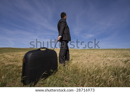 businessman with his luggage outdoor in the field - stock photo
