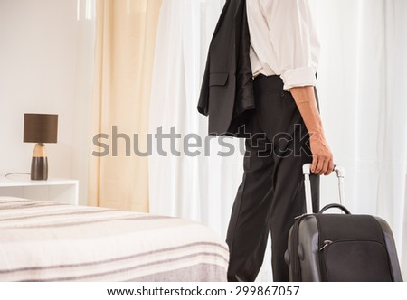 Businessman with his suitcase at the hotel room. Back view. Close-up. - stock photo