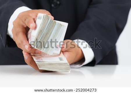 Businessman with huge amount of money - stock photo