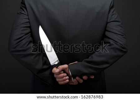 Businessman with knife behind his back - stock photo
