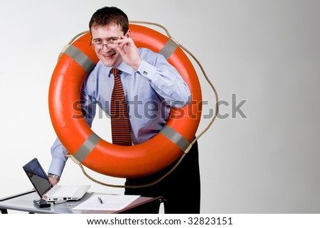 Businessman with laptop and life buoy - stock photo