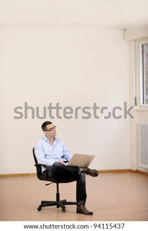 Businessman with laptop in new office  with copyspace - stock photo