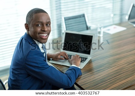 Businessman with laptop in office - stock photo