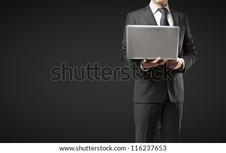 businessman with laptop on a black background - stock photo