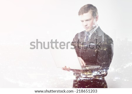 businessman with laptop on a city background - stock photo