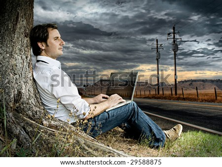 businessman with laptop on a meadow beside a road with dark clouds behind - stock photo
